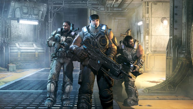"""Main character Marcus Fenix, center, and fellow """"Gears"""" Jace Stratton, left, and Domingo Santiago, right, in a scene from 'Gears of War 3.'"""