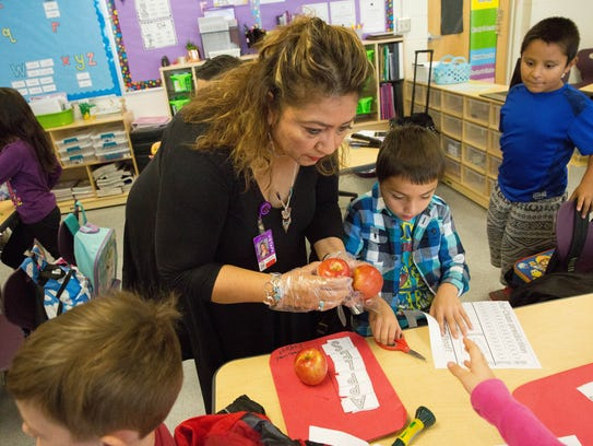 Eloisa Solis, the principle at Valley View Elementary School, hands out Braeburn apples to students in Courtney Degler's first-grade class on Tuesday, October 24, 2017. Students at Valley View and around the district are participating in Apple Crunch week, a program aimed at teaching students about healthy foods that ties into all the
