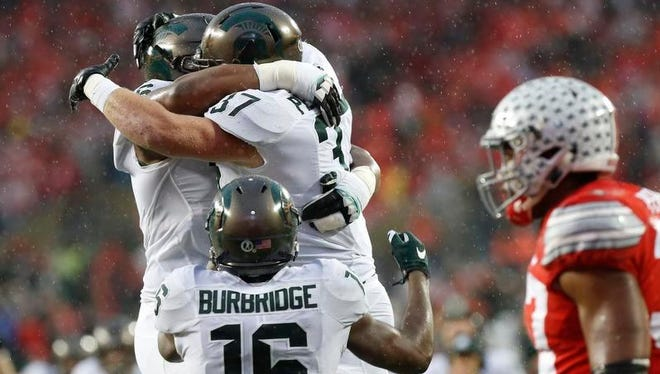 Nov 21, 2015; Columbus, OH, USA; Michigan State Spartans fullback Trevon Pendleton (37) celebrates with Spartans quarterback Damion Terry (6) after scoring a touchdown against the Ohio State Buckeyes in the second quarter at Ohio Stadium.