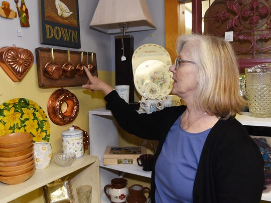 Karen Allan, owner of Pass It On 2 in Pine Plains, shows off a set of copper measuring cups she has displayed on a wooden box lid.