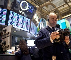 Traders wear 2013 New Year's glasses while they work on the floor of the New York Stock Exchange on Monday in New York City.
