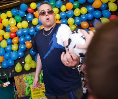 Jason Villano awards a stuffed animal to a winner at his boardwalk balloon-pop amusement game on May 12 in Seaside Heights, N.J.
