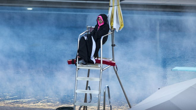 Lifeguard Jessmin Fernandez watches the women's varsity triathlon team practice Jan. 25, 2017, at ASU's Mona Plummer Aquatic Center in Tempe. The outside temperature at the start of the 7:30 a.m. practice was 36 degrees; the water temperature was 80 degrees.