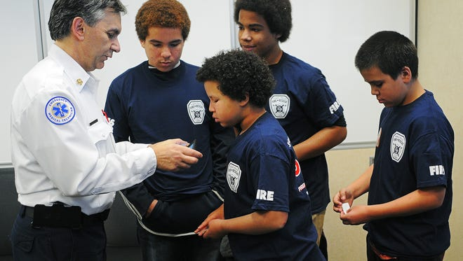 Chief Jim Sideras, with Sioux Falls Fire Rescue, shows, from left, Zavion Holloway, 13, Mystik Holloway, 10, Xaiveor Holloway, 15, and Dymond Holloway, 11, a group photo that he took after a press conference Monday, Dec. 1, 2015, at the Law Enforcement Center in Sioux Falls. The Holloway children and their parents, Marchelle and Michael, were almost killed by carbon monoxide in their home over the weekend, and were rescued by officer Ryan Chase, with the Sioux Falls Police Department.