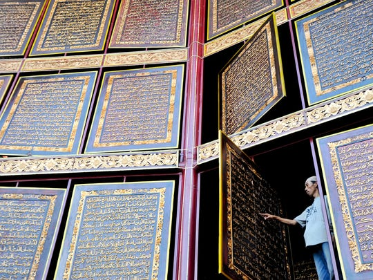A man reading the giant Qur'an in Palembang, Indonesia. This Qur'an was made from wood carvings. At nearly 30 feet tall, it's the world's largest hand-carved Qur'an.