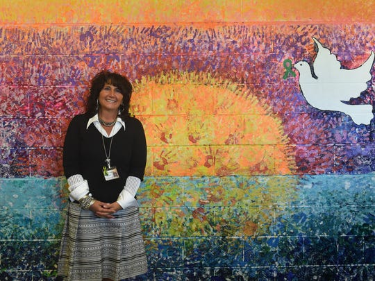 Sparks Middle School principal Stacey Ting-Senini stands at a mural that was painted by a student on a hallway of the school on May 12, 2014.