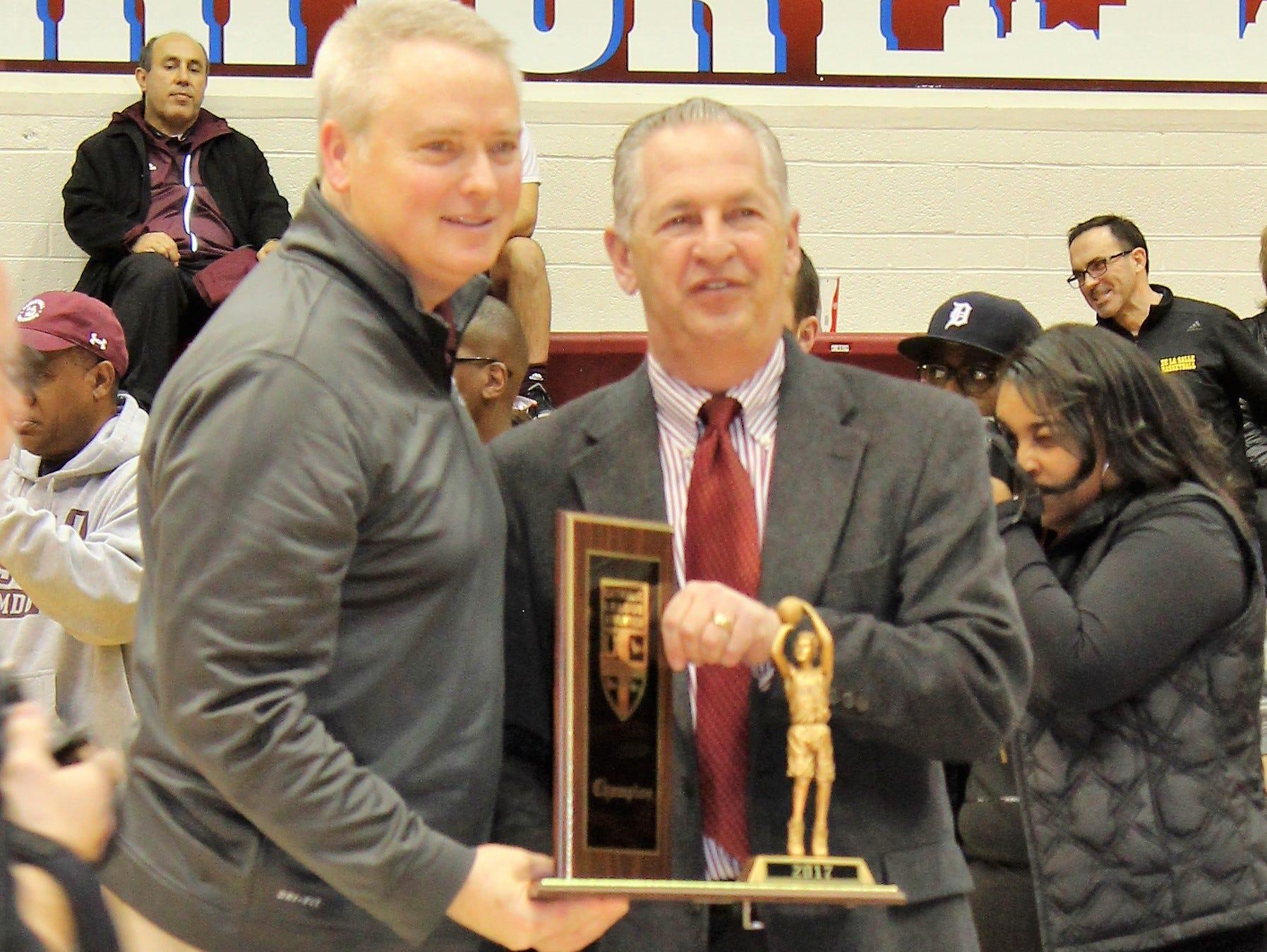 U-D Jesuit coach Pat Donnelly, left, receives the Catholic League championship trophy from league director Vic Michaels.