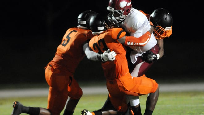 Cocoa defenders swarm the Raines quarterback in the 2014 meeting won by the Tigers.
