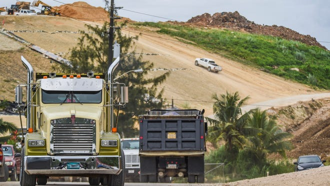 In this file photo, dump trucks and other vehicles enter and leave the site of the former Ordot  dump.