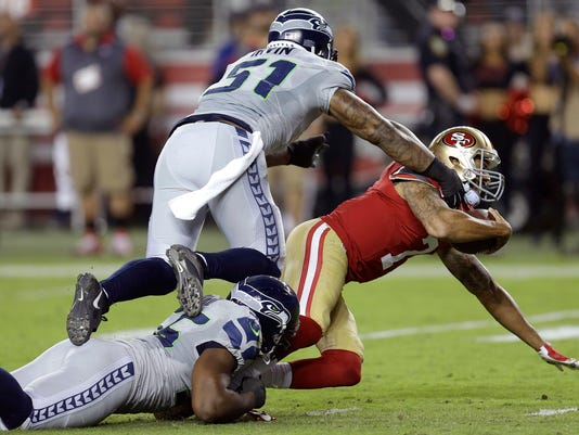 Seattle Seahawks defensive end Cliff Avril, bottom left, sacks San Francisco 49ers quarterback Colin Kaepernick, right, as defensive end Bruce Irvin (51) follows during the first half of an NFL football game in Santa Clara, Calif., Thursday, Oct. 22, 2015. (AP Photo/Ben Margot)