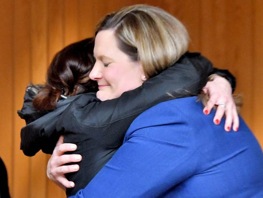 Assistant Attorney General Angela Povilaitis hugs victims