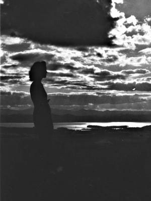 A woman stands at the Mount Philo summit at sunset, circa 1940s. The image was taken by Mac Derick, one of Vermont's earliest promotional photographers.