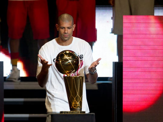 In this June 25, 2012, photo, Miami Heat player Shane Battier looks at the NBA Championship trophy during the public celebration in Miami, after the team won the national championship. Battier was hired Thursday, Feb. 16, 2017, to lead the new analytics department for the Heat, the team he helped win NBA championships in 2012 and 2013. (AP Photo/J Pat Carter)