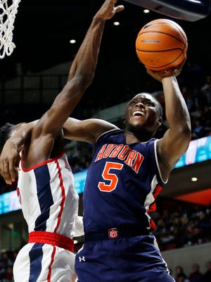 Auburn guard Mustapha Heron (5) battles with a Mississippi defender as he tries a layup during the second half of an NCAA college basketball game in Oxford, Miss., Tuesday, Jan. 30, 2018. Auburn won 79-70.
