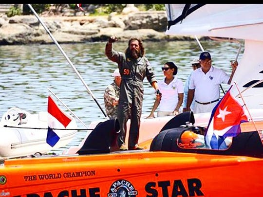 Roger Kuhl waves to the more than 10,000 Cubans who lined Havana harbor Saturday after the Apache Star arrived. Kuhl piloted the boat and set a time and speed record.