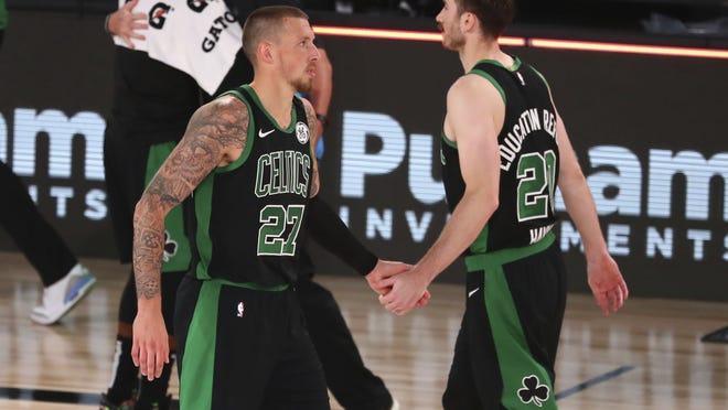 Boston Celtics center Daniel Theis (left) celebrates with teammate Gordon Hayward after defeating the Orlando Magic in an NBA basketball game on Sunday in Lake Buena Vista, Fla.