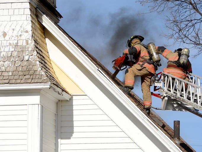 Firefighters use a chainsaw to ventilate the attic while fighting a fire at the Apostolic House of Deliverance on south Duluth Ave. Saturday evening, May 10, 2014.