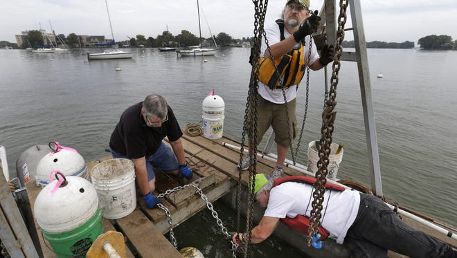 Neenah Nodaway Yacht Club members Terry Smith, left, of Neenah, Brad Bingham of Neenah, and harbor master John Ross of Oshkosh replace mooring chains Wednesday near the boardwalk at Riverside Park in Neenah. The group plans to inspect, repair or replace 90 moorings. According to commodore Don Reid, the club was founded in 1864. It was originally named the Neenah Yacht Club and was founded by Charles Doty and a few others.