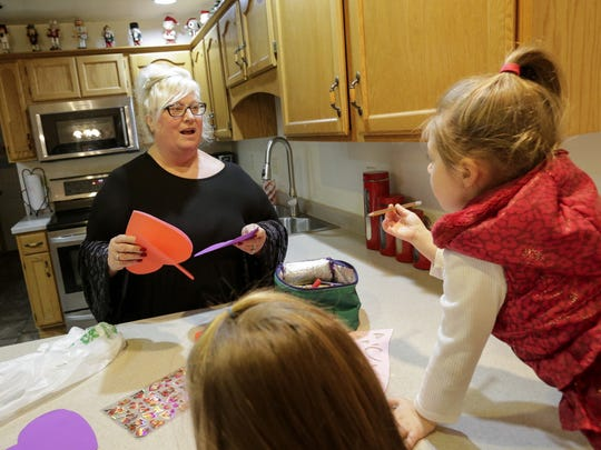 Becky Brooks talks to her adopted daughter Anna, 3, while setting up arts and crafts for the kids in their kitchen Wednesday, Jan. 24, 2018, in Manitowoc.