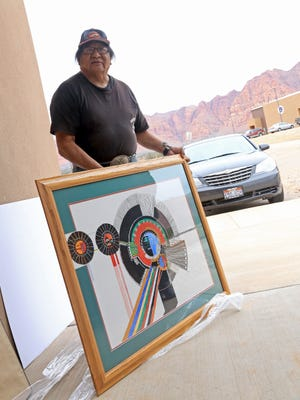 Artist Daniel Growler, a member of the Cedar Band of Paiutes, presents one of his paintings on Feb. 10 to the Shivwits Medical Clinic on the Shivwits Paiute Indian Reservation.