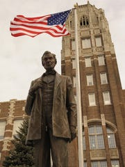"Exterior of Manitowoc Lincoln High School with the Abraham Lincoln ""Abe"" bronze statue and the American flag."