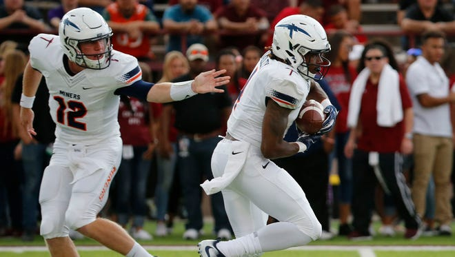 UTEP quarterback Ryan Metz hands off the ball to running back Quardraiz Wadley for a short gain during the Miners' game against the NMSU Aggies on Saturday night in Las Cruces.