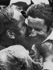 Andy Granatelli gives Mario Andretti a kiss after he