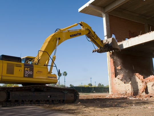 Heavy equipment is used to knock down a wall of the
