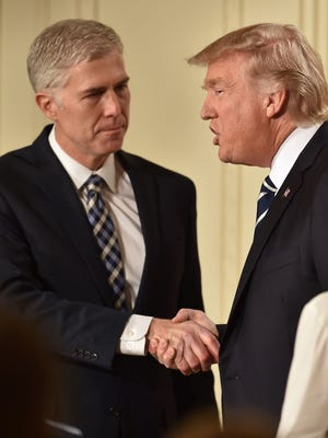 Judge Neil Gorsuch (L) shakes hands with US President Donald Trump after he was nominated for the Supreme Court, at the White House in Washington, DC, on January 31, 2017.