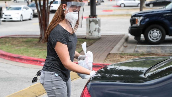 April Romero Brown distributes free masks, gloves, and hand sanitizer to Dove Springs residents on July 15 after recent data show the area has the highest number of coronavirus cases in Travis County.