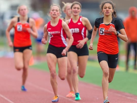 Northville freshman Yasmine Mansi (5) sprints home to a first in the 1,600 ahead of Churchill's Gabrielle Swider and Grand Blanc's Caitlin Rose (middle).