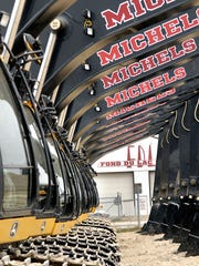 Michels Corp. excavators are lined up, waiting to get