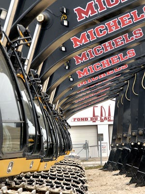 Michels Corp. excavators are lined up, waiting to get Michels decals, at Fond du Lac Stone on state Highway 175 in this 2006 file photo.
