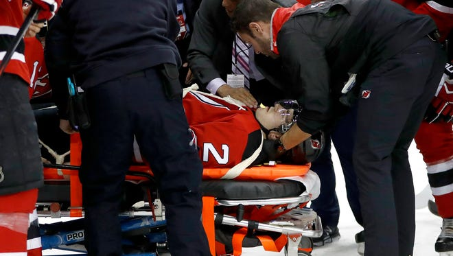Trainers load New Jersey Devils defenseman John Moore onto a stretcher to pull him off the ice after he was injured during the first period against the Washington Capitals on Saturday.