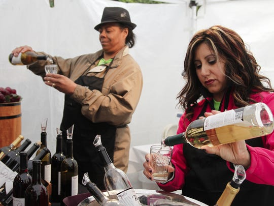 Volunteers Leslie Grannell and Ester Reyes pour Burgdorf's Winery samples at the Potter Park Zoo's 2014 Wine & Stein event.