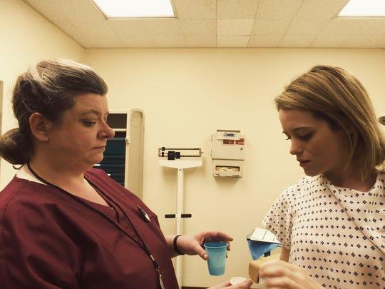 "In ""Unsane,"" Nurse Boles (Polly McKie, left) checks"