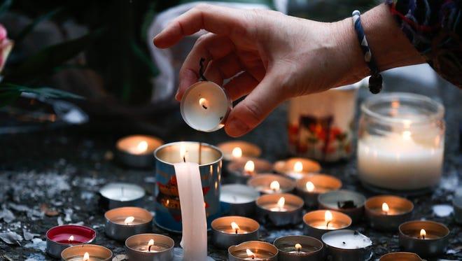 A woman lights a candle Nov. 14 near the Bataclan concert venue in Paris.