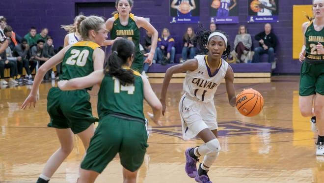 Calvary Day's Jasmine Akins (11) drives toward the basket as Savannah Country Day's Rachel Wollenburg (20) and Catherine Goodman (14) defend duing a game last season at Calvary.