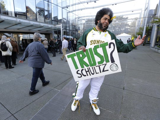 "In this March 18, 2015 file photo, Kris Brannon, who is known as ""Sonics Guy"" for his efforts to bring an NBA basketball team back to Seattle, holds a sign that reads ""Trust Schultz?"" as he greets attendees arriving for Starbucks Corp.'s annual shareholders meeting in Seattle."