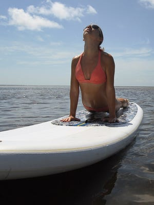 Combining two great activities, paddleboarding and yoga, could be a hit in the Pensacola area this summer.