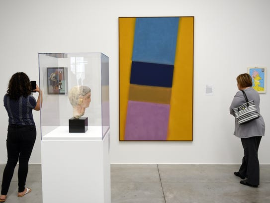 Guests look at art in the gallery space during a preview