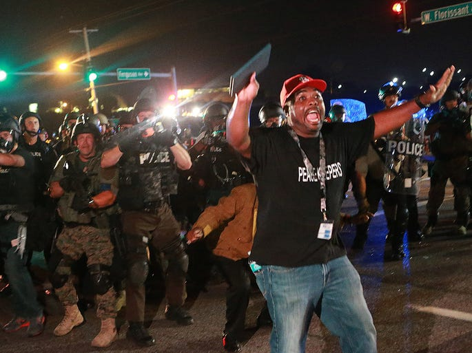 A citizen peacekeeper tries to keep protesters back as police advance on Aug. 18 in Ferguson, Mo. The Aug. 9 shooting of Michael Brown by a police officer has touched off demonstrations in the St. Louis suburb where police have used riot gear and tear gas against protesters.