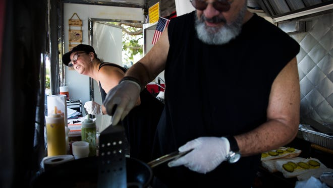 Julie Dana pokes her head out of JewBan's Deli Dˆle to take a customer's order as her husband, Ray Garcia prepares a Cuban steak bowl on Tuesday, April 4, 2017 in the parking lot of the NCH Business Offices and White Elephant Thrift Store in North Naples. The food truck serves Jewish and Cuban food.
