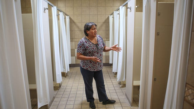 Claudia Castorena of the Galilee Center gives a tour of the shower facilities that are used by the migrant community in Mecca, March 8, 2017.