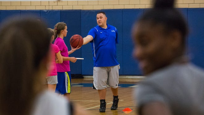Robert E. Lee's new girls basketball coach, Josh McElheny, goes over drills with his players during their first day of practice on Monday, Nov. 9, 2015.