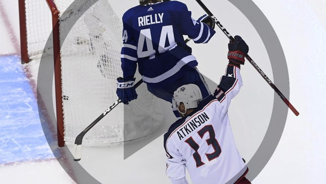 Columbus Blue Jackets right wing Cam Atkinson (13) celebrates his goal as Toronto Maple Leafs defenseman Morgan Rielly (44) skates nearby during the third period of an NHL hockey playoff game in Toronto, Sunday, Aug. 2, 2020.
