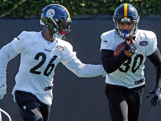 Pittsburgh Steelers running backs Le'Veon Bell (26) and James Conner run a drill during a team practice at the NFL football team's training facility in Pittsburgh, on Monday, Sept. 4, 2017. It was Bell's first workout with the team. (AP Photo/Gene J. Puskar)