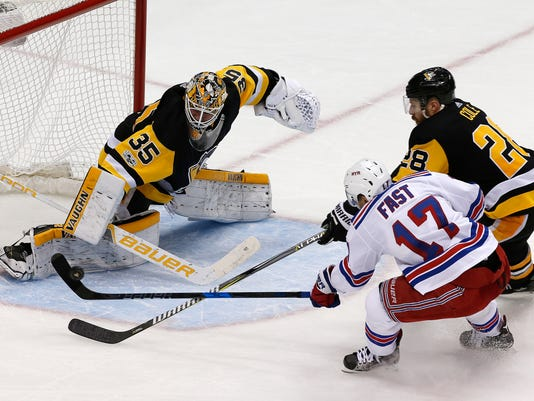 Pittsburgh Penguins goalie Tristan Jarry (35) blocks a shot by New York Rangers' Jesper Fast (17) with Ian Cole (28) defending during the third period of an NHL hockey game in Pittsburgh, Tuesday, Dec. 5, 2017. The Rangers won 4-3. (AP Photo/Gene J. Puskar)