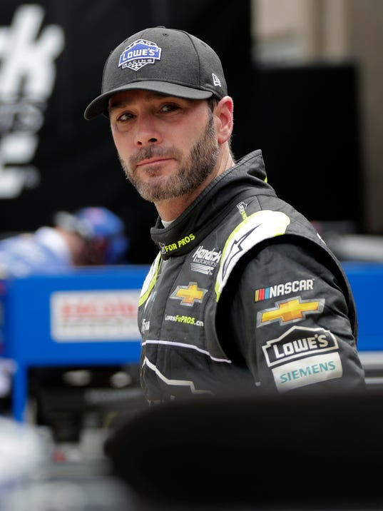 Jimmie Johnson walks out of the garage area after a practice session for a NASCAR Cup series auto race in Fort Worth, Texas, Friday, April 6, 2018. (AP Photo/Tony Gutierrez)