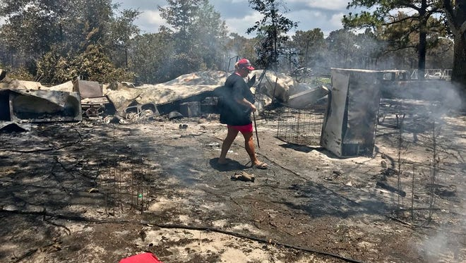 Jody Lively of Eastpoint looks around for old pictures or anything else left from a forest fire that destroyed her home on Wilderness Road.
